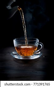 Pouring  tea in glass cup on black  background, liquid movement in a cup, low key