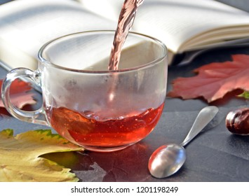 Pouring tea in a glass in front of an autumnal setting with chestnuts, colorful autumn leaves and a book - drinking tea to warm up on cold winter days symbolized by a glass of tea in autumn setting