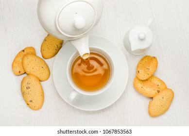 pouring tea into cup on white table with cookies and milk jug