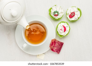 pouring tea on white table with christmas cupcake