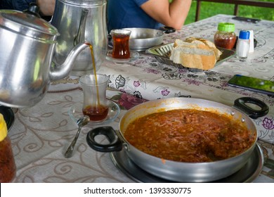 """Pouring tea from tea pot to glass. Breakfast preparation concept. Traditional Turkish brewed tea drink in morning also as known """"Cay"""" or """"Turk Cayi"""". Menemen and bread with Turkish Tea."""