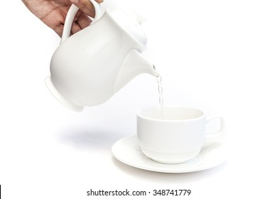 Pouring tea from teapot into a cup