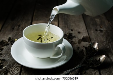 Pouring tea in white cup, rustic wood background