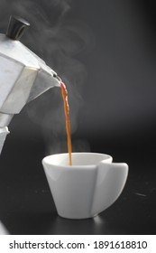 Сoffee is pouring from a teapot into a white cup on a black background and steam is coming