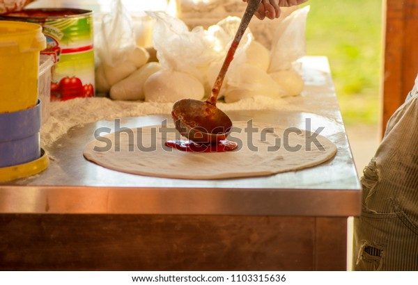 Pouring tomato sauce on pizza dough with metal ladle.Cooking pizza against open window in bakery.