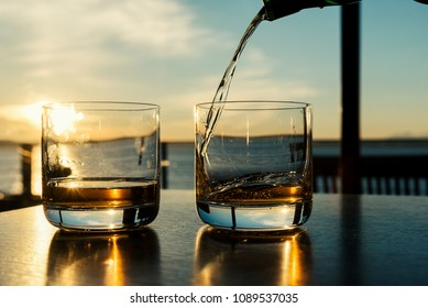 Pouring two glasses of whiskey at sunset on indoor table with large sea view windows.