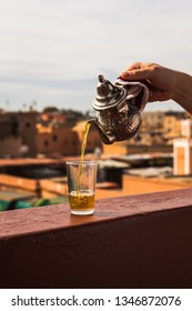 Pouring typical Morrocan fresh mint tea from a silver karraffe into a tea glass above the roofs of the Medina of Marrakesh (Marrakesh, Morocco, Africa)