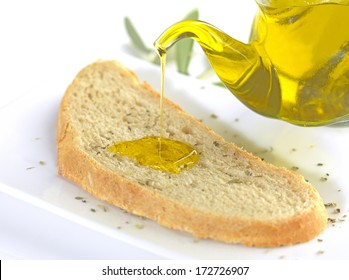 pouring virgin olive oil on a slice of bread with oregano