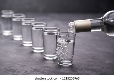 Pouring vodka into the glass on a black background, selective focus