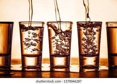 Pouring vodka into transparent glass vodka shots. Orange bubble alcohol drink background.