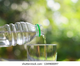 Pouring water from bottle into glass over nature  background.