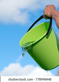 Pouring water and bucket against blue sky.