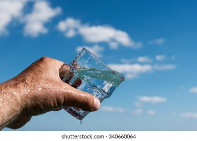 Pouring water in glass against nature background.