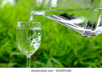 pouring water in glass on green background