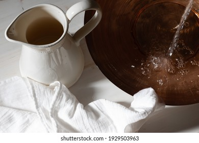 Pouring water into basin by pitcher and linen cloth