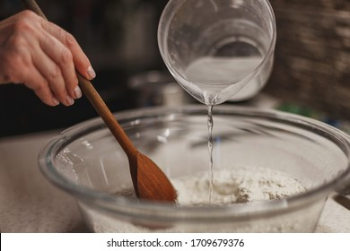 Pouring water into dry dough mixture while mixing it with wooden spoon