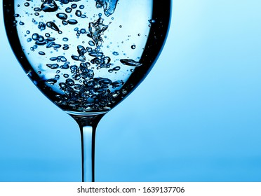 Pouring water into a glass against light blue background. fresh water a glass with bubbles blue background