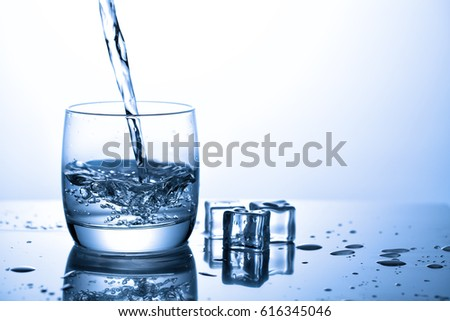 Pouring water from into glass near ice cubes with splashes.