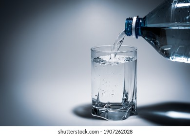 Pouring water into a glass from a plastic bottle. Light contrasting background with veneering.