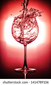 Pouring water into glass and splash out of a glass isolated on bright red and black background