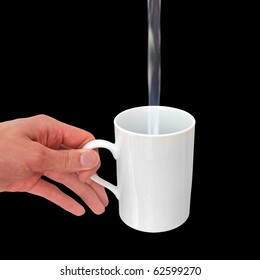 Pouring water into a white mug isolated on black background