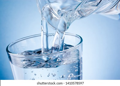 Pouring water from jug into glass on blue background