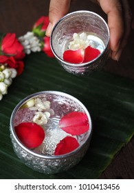 Pouring water on revered adults' hands for blessing on Songkran Day (Thai New Year/Thai water festival). Use silver blessing bowl of water, jasmine and rose petals and traditional garland.