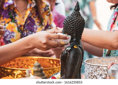 Pouring water onto a Buddha Statue in Songkran day festival, Thailand.