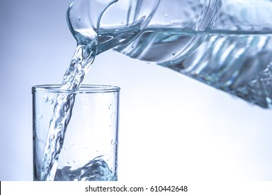Pouring water from pitcher into a glass