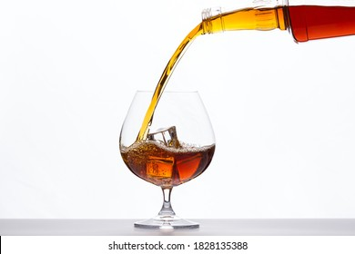 Pouring whiskey drink into glass with ice cubes on white background