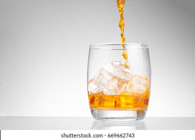 pouring whiskey in glass with ice