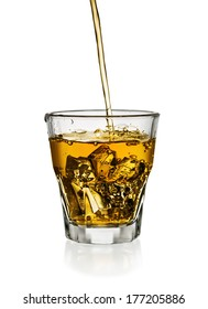 Pouring whiskey in glass with ice isolated on white
