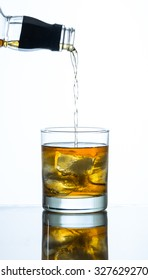 pouring whiskey into a glass of ice