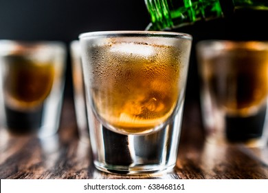 Pouring Whiskey Shots with ice on dark wooden surface.