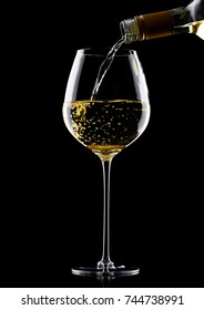 Pouring white wine from bottle to glass isolated on black background
