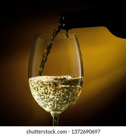 Pouring white wine from a bottle into a wine glass on a black background. Close-up studio shot.