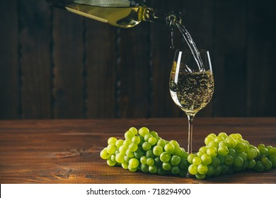 Pouring white wine from the bottle into a glass with a bunch of green grapes against wooden background with free space