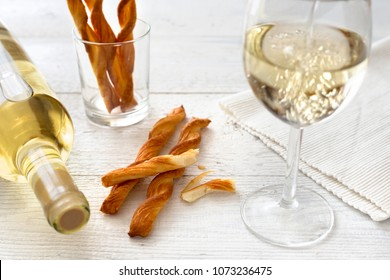 Pouring white wine into a glass next to grissini and wine bottle on rustic white wooden table.