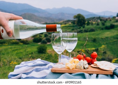 Pouring white wine into the glasses at a picnic in the mountains