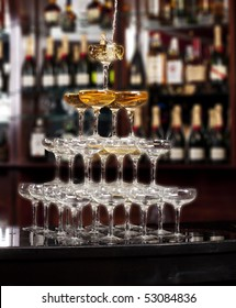 Pouring the wine along stack of glasses