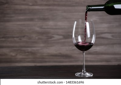 Pouring wine from bottle into glass on table against wooden background, space for text