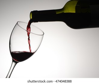 Pouring wine in a glass on white background