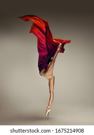 Pouring wine. Graceful classic ballerina dancing on grey studio background. Tender red cloth. The grace, artist, movement, action and motion concept. Looks weightless, flexible. Fashion, style.