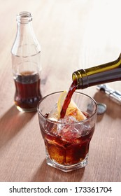 Pouring wine into kalimotxo mixture glass on wooden table