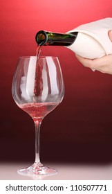 Pouring wine into wineglass on red background