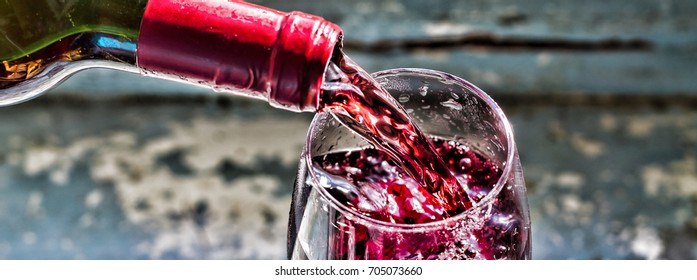 Pouring wine, pouring red wine. Women's Day, 8 March.  Wine in a glass, selective focus, motion blur, Red wine in a glass.