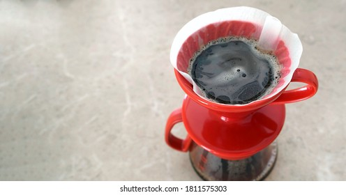 Pourover. v60. Delicious aromatic coffee filter is brewed in a red ceramic dropper. Close-up, view from above
