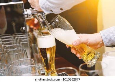 pours beer into a glass from a tap, hands in the frame
