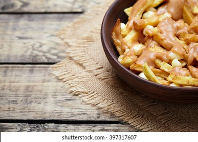 Poutine Canadian homemade traditional fast food meal with fries, curd cheese, gravy and beer on vintage wooden table background. Empty space for design text template. Rustic style,