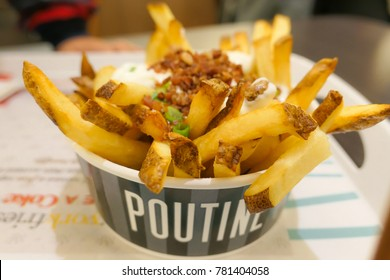 Poutine traditional Canadian meal with fries, curd cheese and sauce on the table.